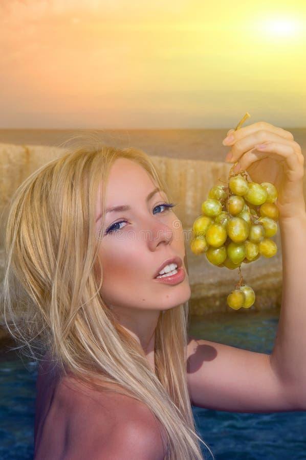 Meisje met druiven op een strand stock fotografie