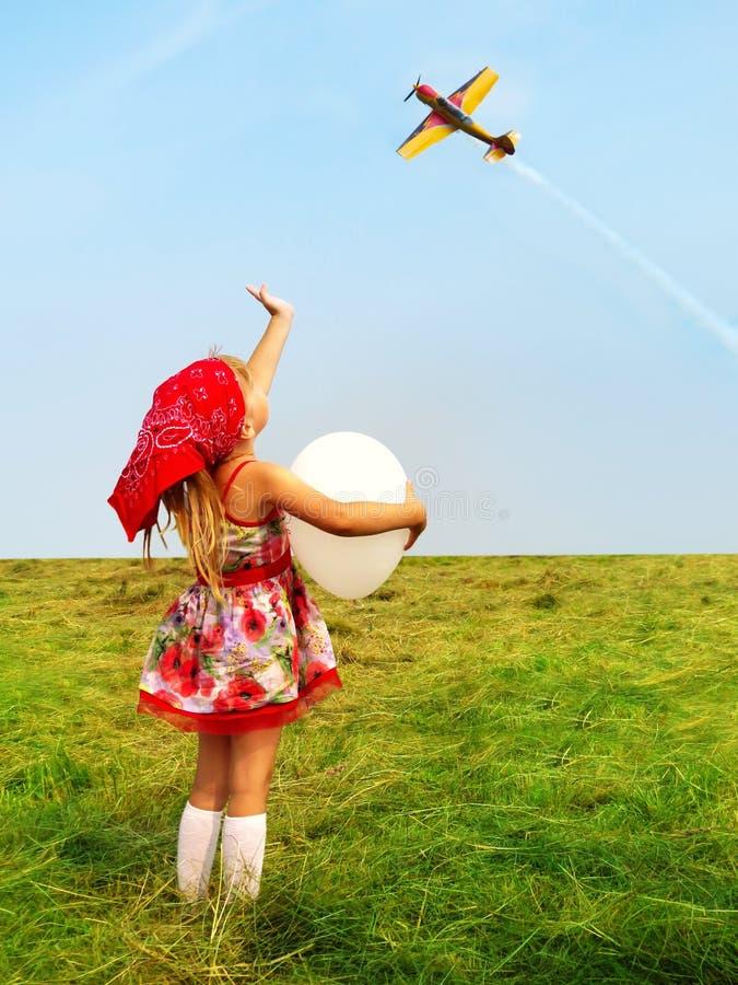 Meisje met een ballon die een hand vliegend vliegtuig golven royalty-vrije stock afbeeldingen