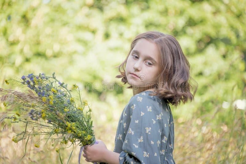 Meisje met een boeket van wilde bloemen, portret stock afbeelding