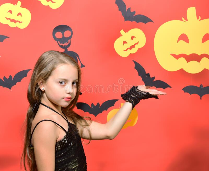 Meisje met een ernstig gezicht op rode achtergrond met vleermuizen, pompoenen royalty-vrije stock foto