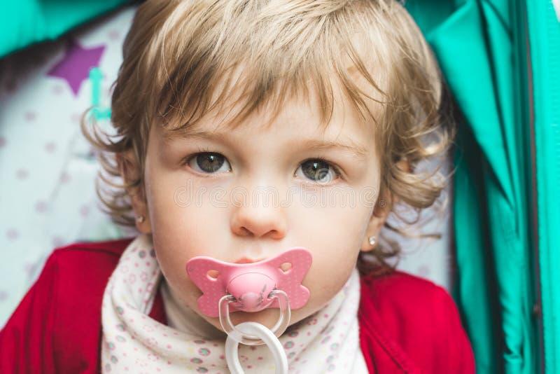 Meisje met een fopspeen in haar mond royalty-vrije stock afbeelding