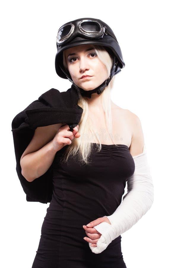 Meisje met een gebroken wapen in pleister, die motorfietshelm dragen stock afbeeldingen