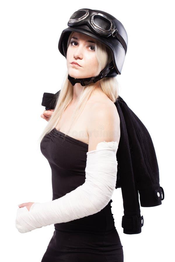 Meisje met een gebroken wapen in pleister, die motorfietshelm dragen royalty-vrije stock afbeeldingen