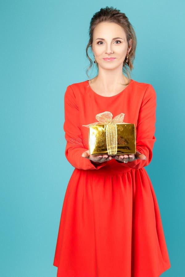 Meisje met een gift in een rode kleding op een blauwe achtergrond stock afbeelding