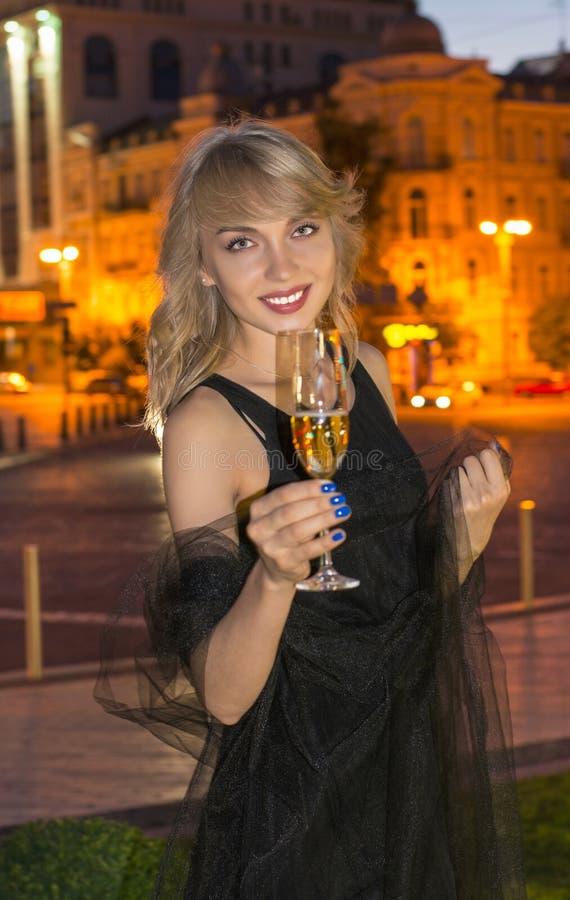 Meisje met een glas champagne bij nacht stock afbeelding