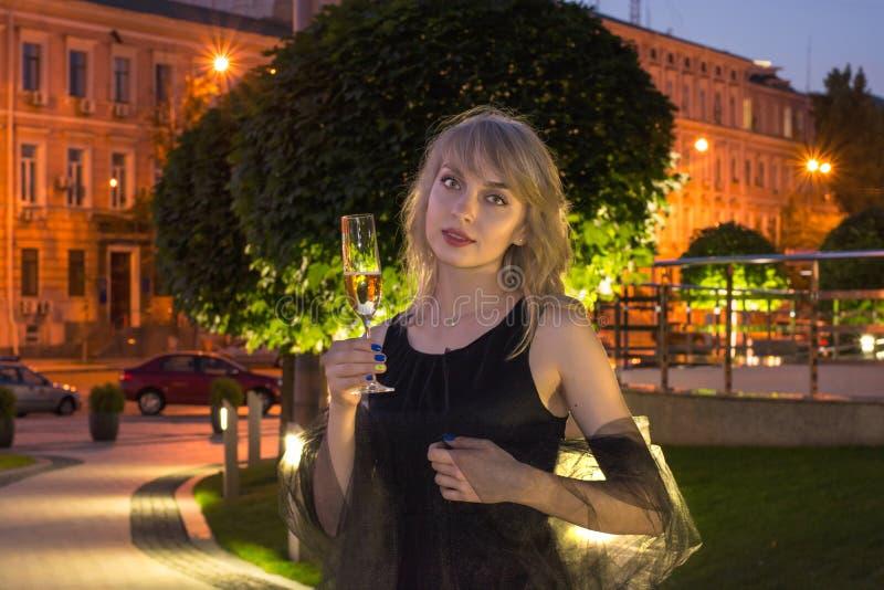 Meisje met een glas champagne in de stad stock fotografie