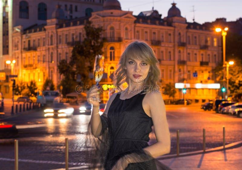 Meisje met een glas champagne in de stad royalty-vrije stock afbeelding