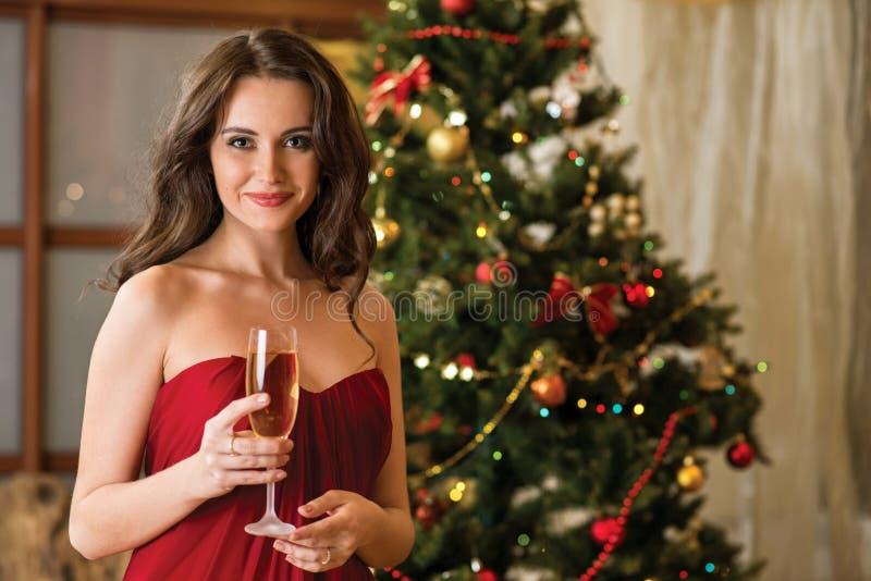 Meisje met een glas champagne op de boom van het nieuwe jaar royalty-vrije stock afbeelding