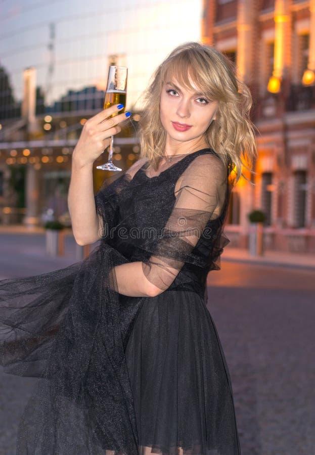Meisje met een glas champagne voor de stad stock foto's