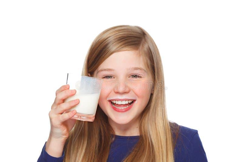 Meisje met een glas melk en van de melksnor het glimlachen stock afbeeldingen