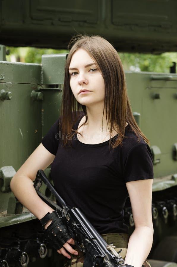 Meisje met een kanon, die dichtbij de pantserwagen stellen stock afbeelding