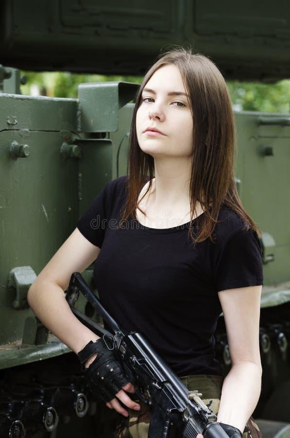 Meisje met een kanon die zich dichtbij de pantserwagens bevinden stock afbeelding