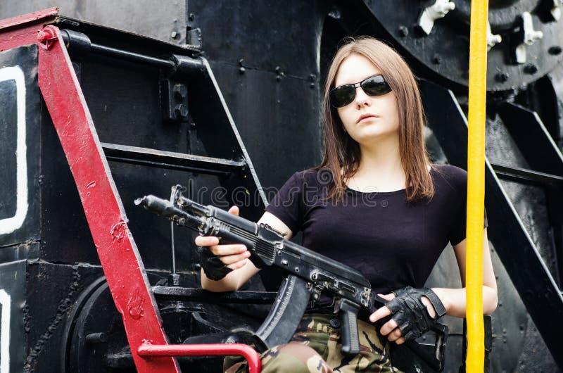 Meisje met een kanonzitting op de lopende raad van een stoomlocomotief royalty-vrije stock foto