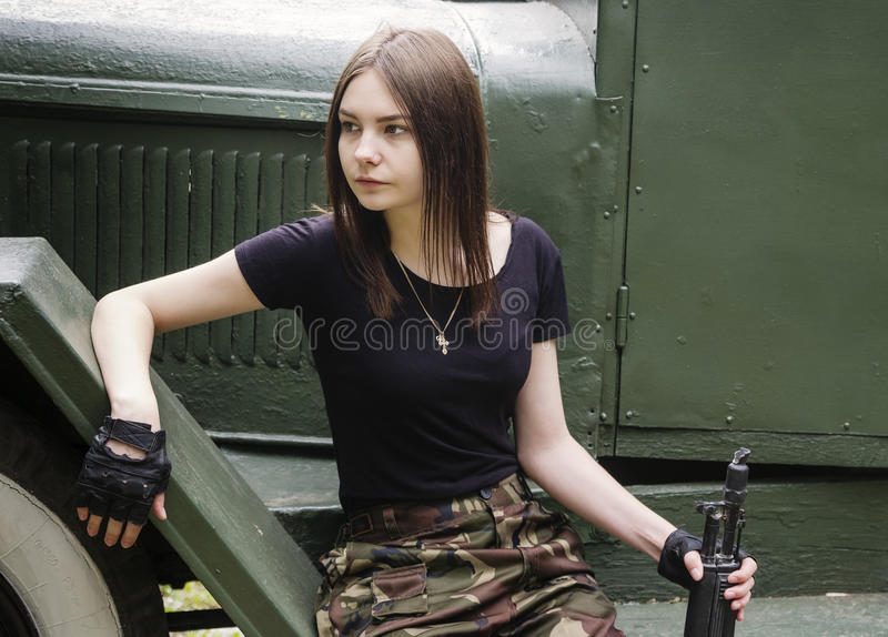 Meisje met een kanonzitting op de stappen van legervrachtwagen stock afbeelding