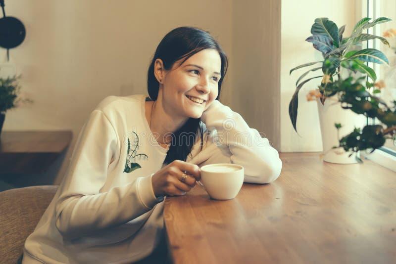 Meisje met een kop van koffie bij het venster in koffiewinkel het glimlachen royalty-vrije stock fotografie