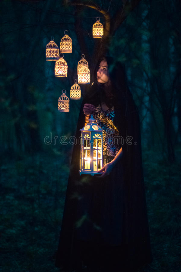Meisje met een lantaarn bij nacht in het bos stock fotografie