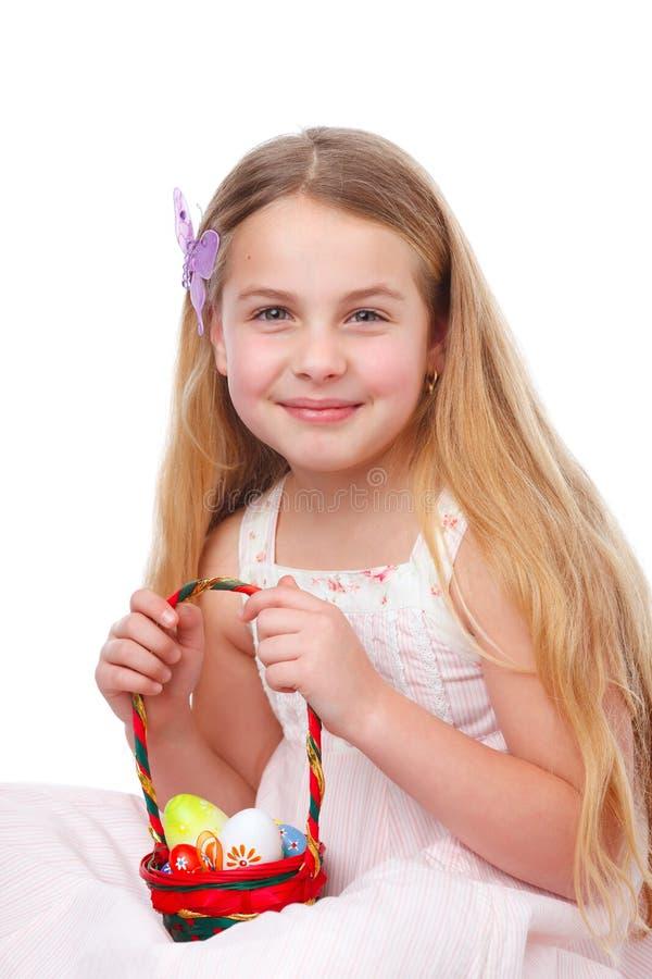 Meisje met een mandhoogtepunt van paaseieren stock foto