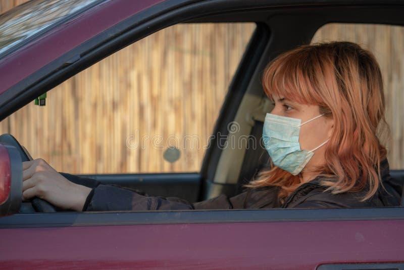 Meisje met een medisch masker in de auto Vrouw met een masker, geschreven COVID-19, ter bescherming tegen het coronavirus Rijauto royalty-vrije stock foto
