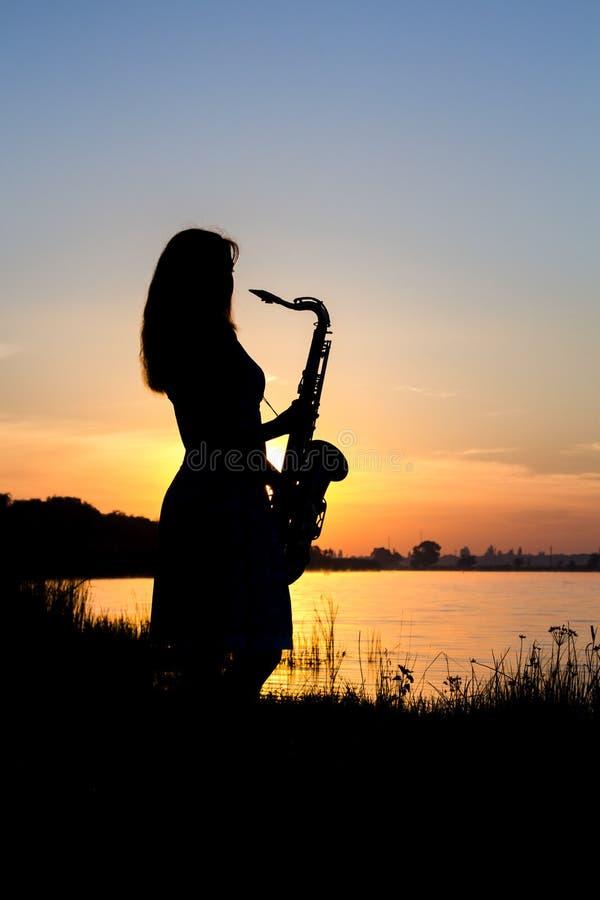 Meisje met een messings muzikaal instrument in de afstand royalty-vrije stock afbeeldingen
