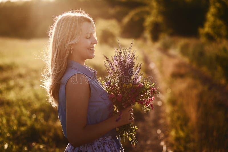 Meisje met een mooi boeket van wild bloemengebied royalty-vrije stock foto