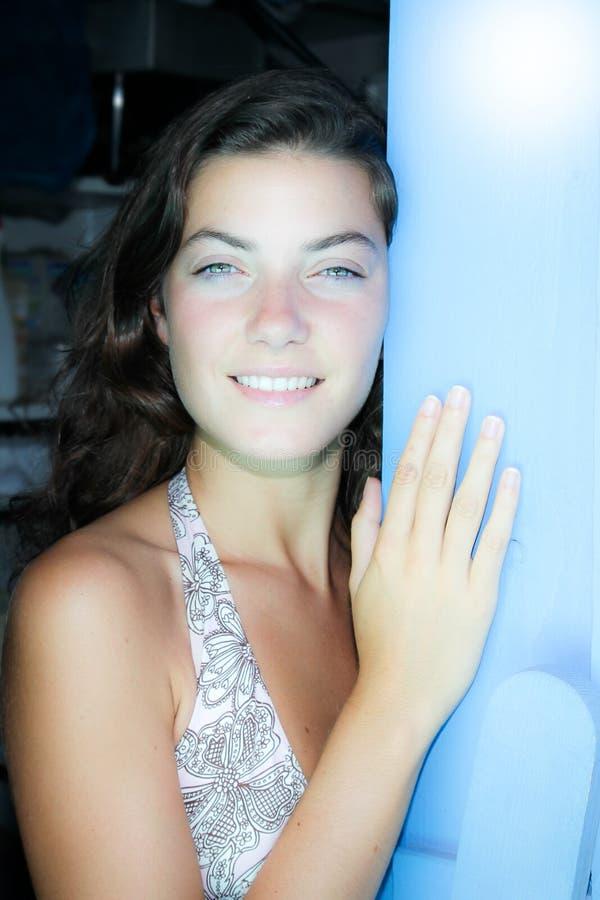 Meisje met een mooi gezicht dichtbij houten blauwe deur stock foto's