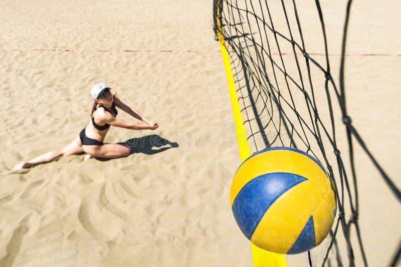 Meisje met een ontevreden gezichtsdalingen op zand die bal raken in netto Het verliezen van het kampioenschap in strandvolleyball royalty-vrije stock fotografie