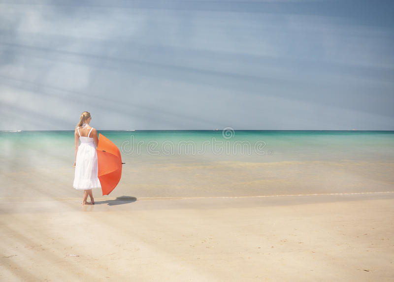 Meisje met een oranje paraplu op het strand royalty-vrije stock fotografie