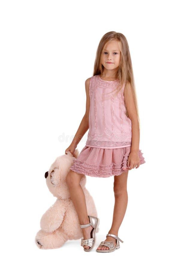 Meisje met een pluchestuk speelgoed op een witte achtergrond wordt geïsoleerd die Slim jong geitje met een teddybeer Kinderjarenc stock afbeeldingen