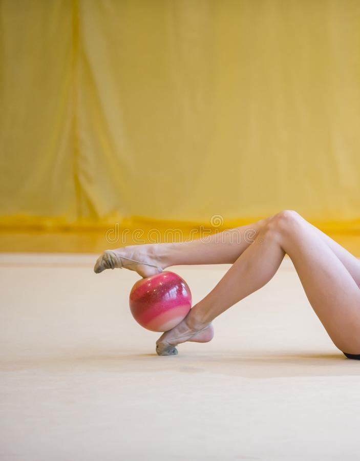 Meisje met een ritmische gymnastiek rode bal Flexibiliteit in acrobaat royalty-vrije stock afbeelding