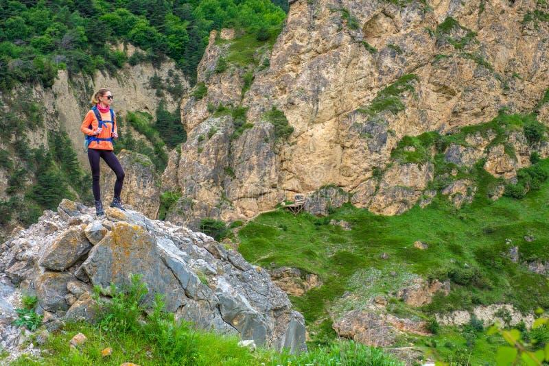 Meisje met een rugzak in de bergen stock foto's