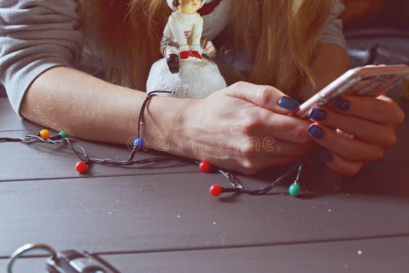 Meisje met een smartphone en Kerstmisspeelgoed royalty-vrije stock afbeelding