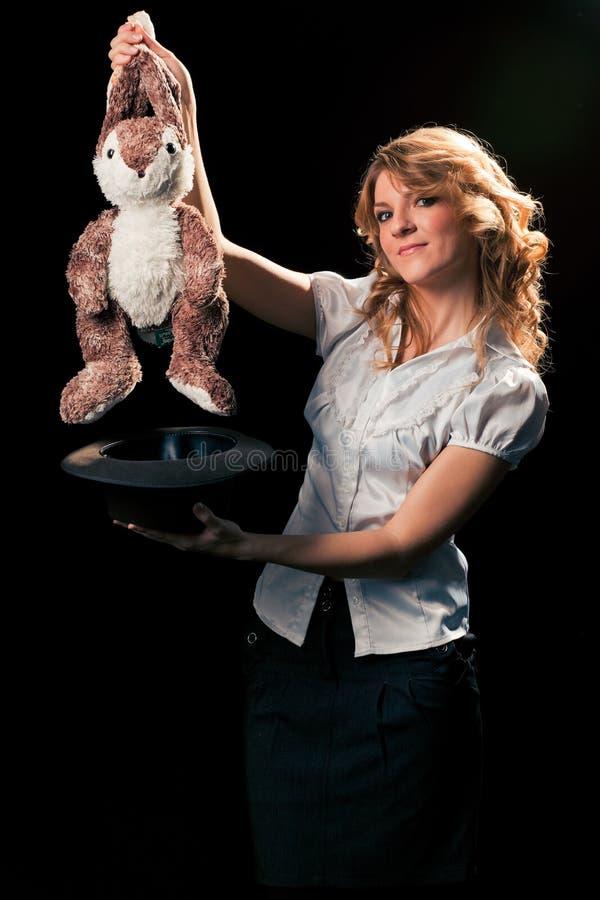 Meisje met een stuk speelgoed konijn uit de hoed wordt gekregen die royalty-vrije stock foto's