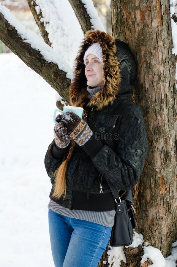 Meisje met een tegen een boom leunen en mok die thee omhoog eruit zien stock fotografie