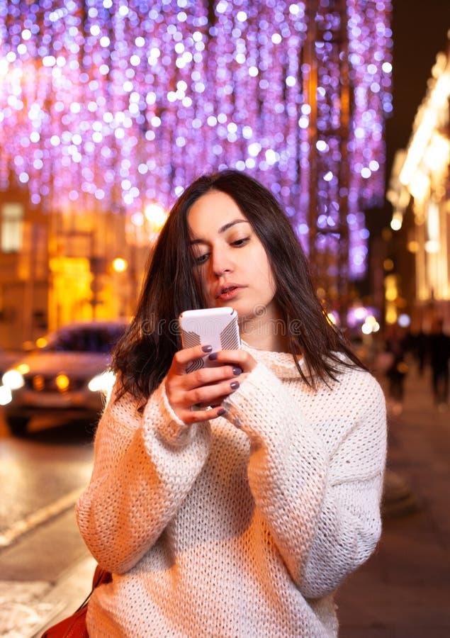 Meisje met een telefoon op de straat van de avondstad stock afbeeldingen