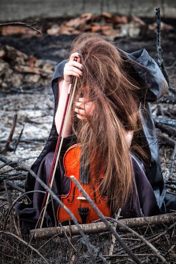 Meisje met een vioolzitting op de as royalty-vrije stock fotografie