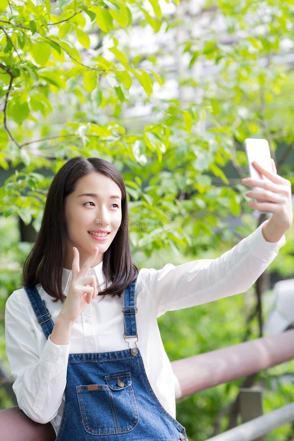 Meisje met een zelf-tijdopnemer van de celtelefoon stock afbeelding
