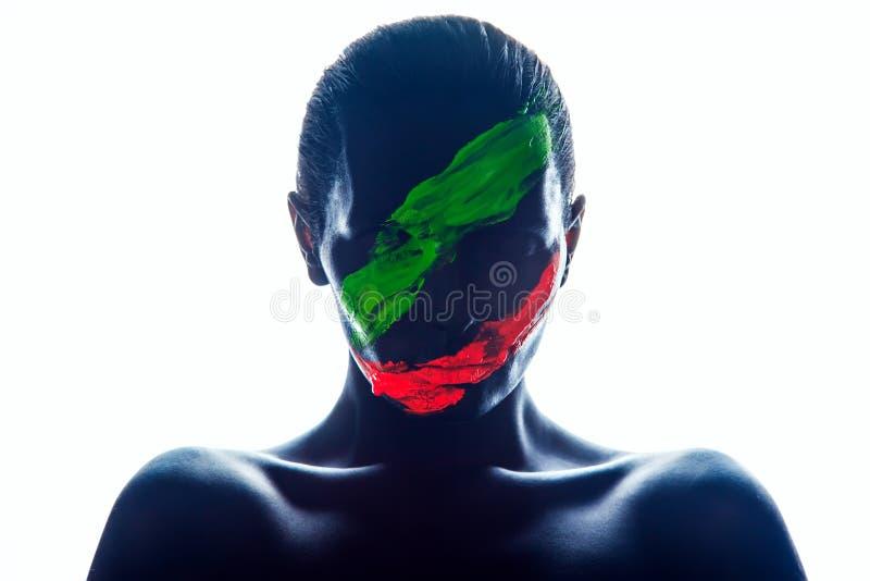 Meisje met een zwarte verf op het gezicht Groen en rood royalty-vrije stock foto