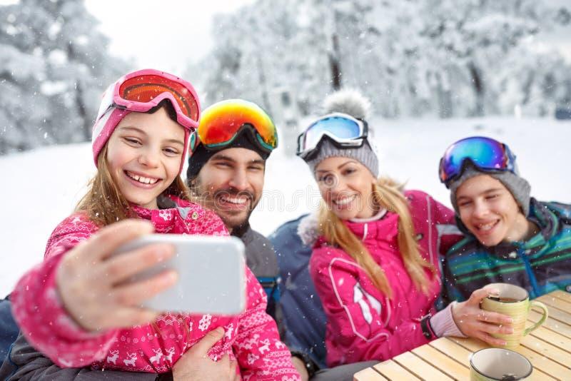 Meisje met familie die selfie terwijl het rusten van het ski?en nemen stock afbeelding