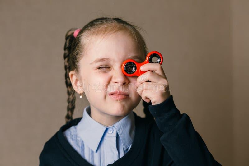 Meisje met Fidget Spinner aan zijn ogen wordt gesteund dat stock afbeelding