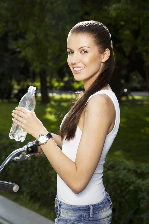 Meisje met fiets en fles water stock afbeelding