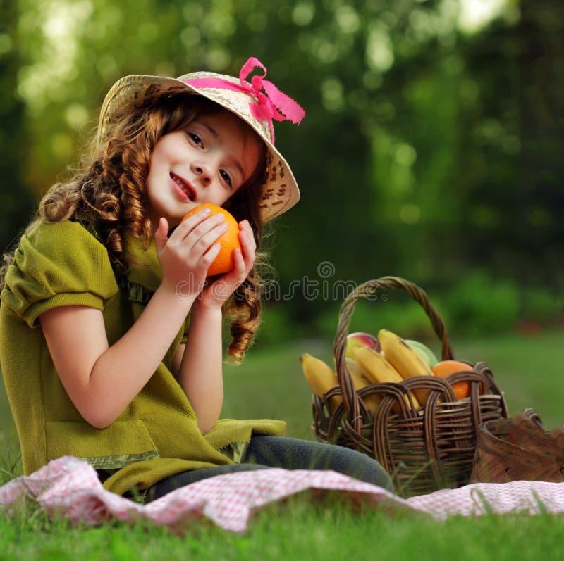 Meisje met fruit in parkpicknick royalty-vrije stock afbeelding