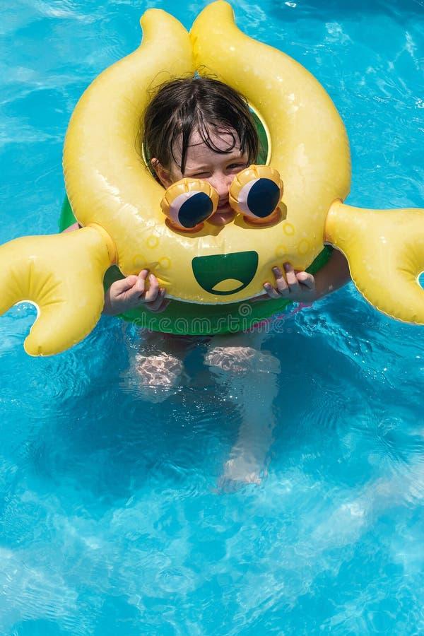 Meisje met gele krabstuk speelgoed vlotter in binnenplaatspool royalty-vrije stock fotografie