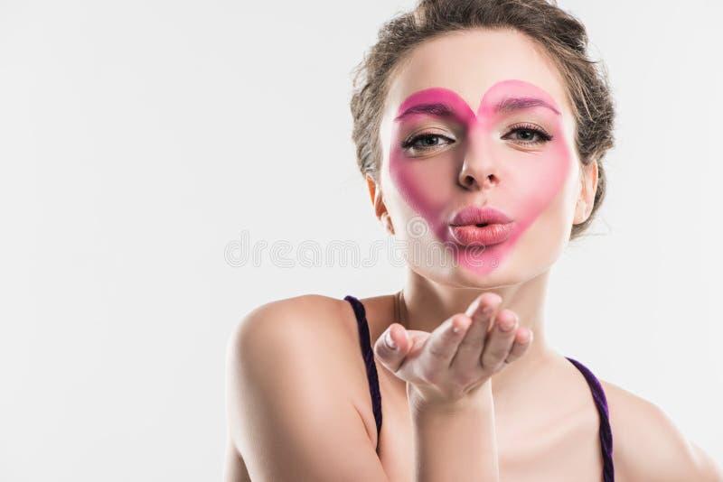 meisje met geschilderd roze hart op gezicht die luchtkus verzenden stock fotografie