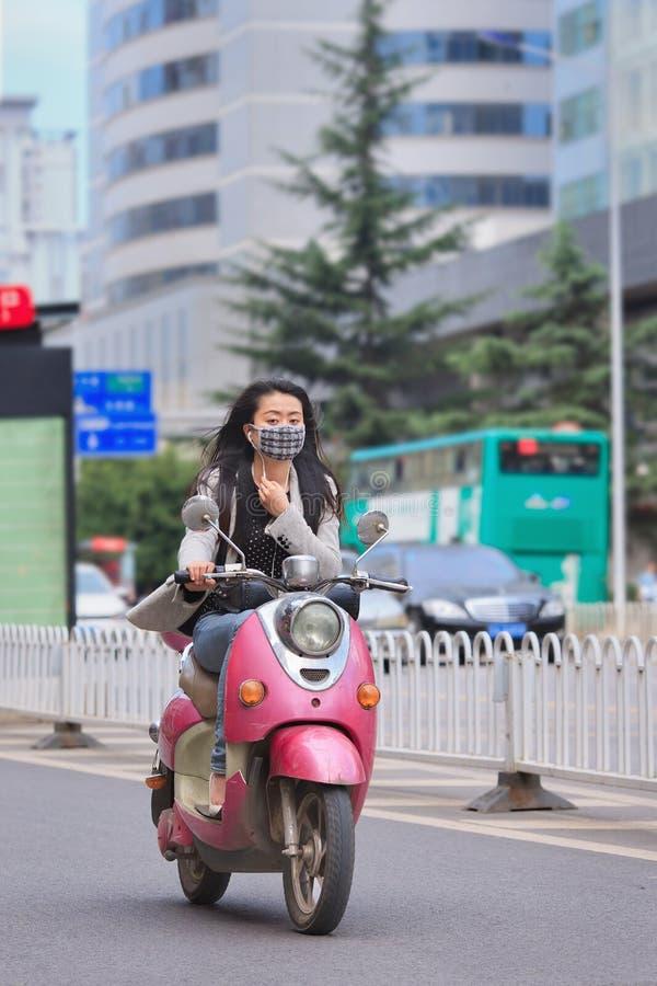 Meisje met gezichtsmasker op retro ontwerp e-fiets, Kunming, China royalty-vrije stock foto's