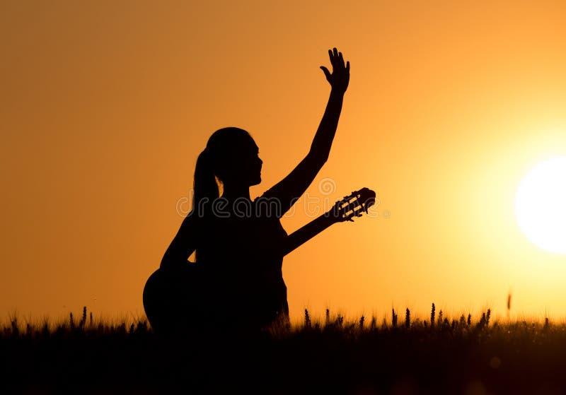 Meisje met gitaar bij zonsondergang royalty-vrije stock afbeeldingen