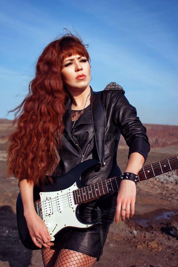 Meisje met gitaar in leerjasje royalty-vrije stock afbeeldingen