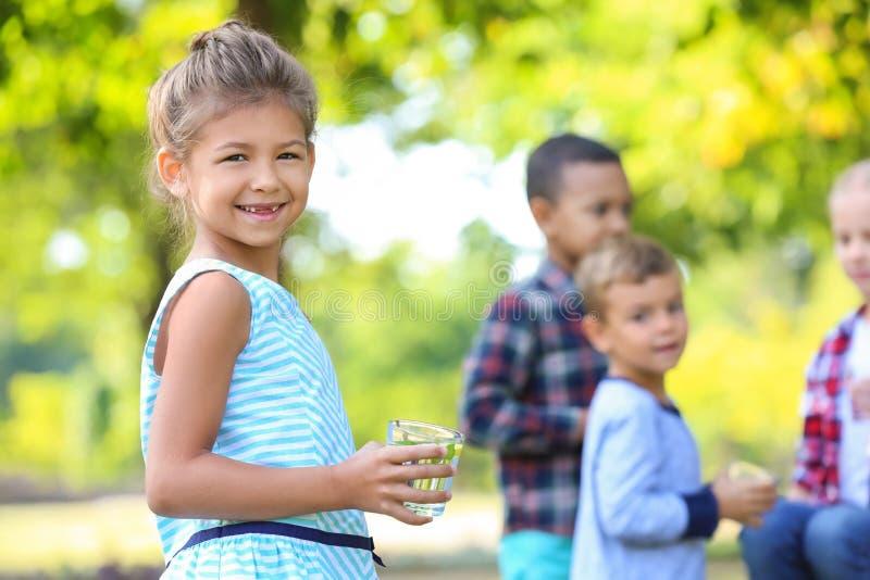 Meisje met glas die natuurlijke limonade in park rusten royalty-vrije stock afbeelding