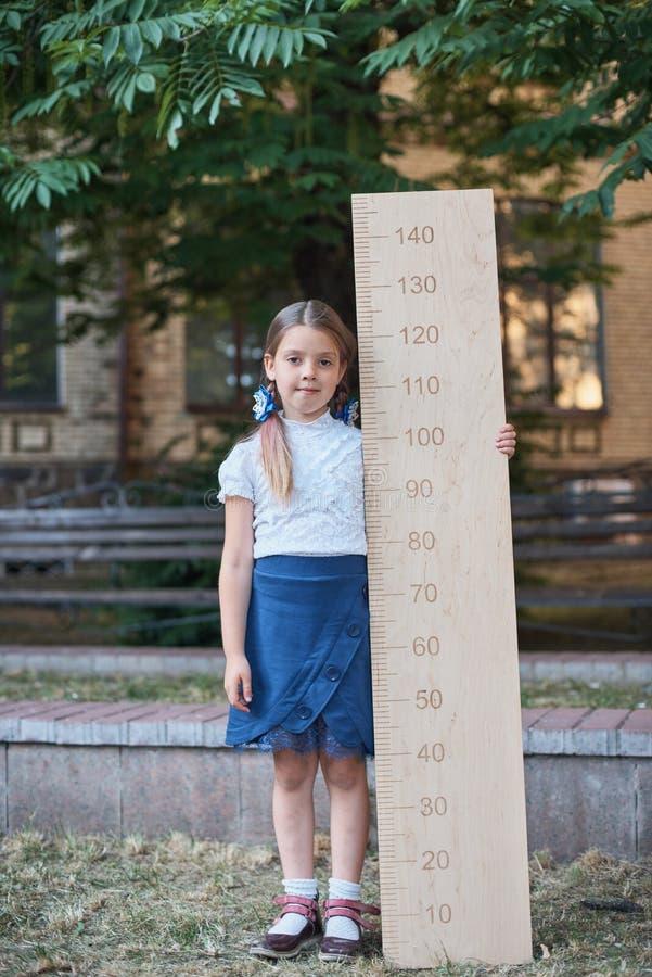 Meisje met grote heerser status op parkachtergrond Afscheidsklok Dag van kennis Begin van het schooljaar Onderwijs en stock foto's
