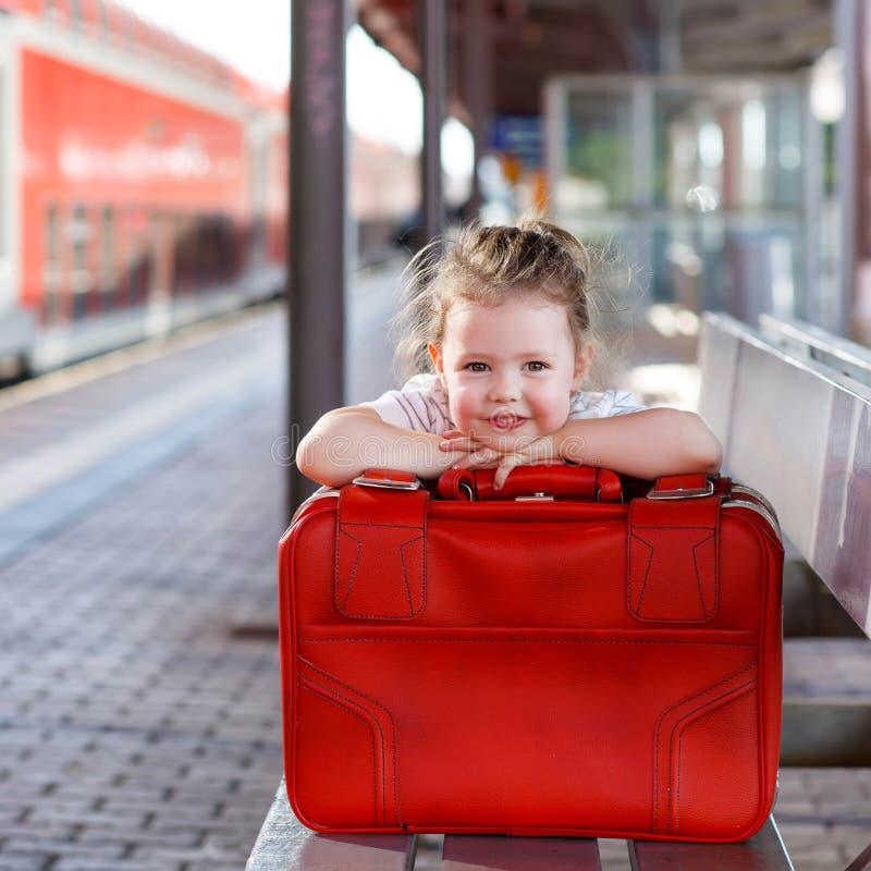 Meisje met grote rode koffer op een station stock fotografie