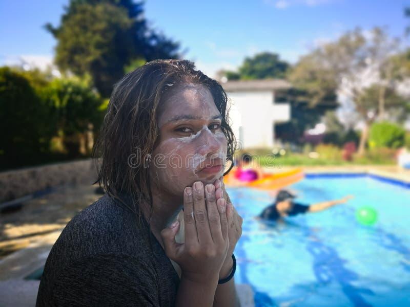 Meisje met haar die gezicht in zonnescherm en uitdrukking van zorg, consternatie wordt behandeld royalty-vrije stock foto's